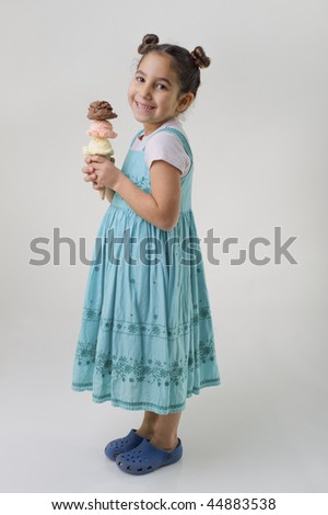little girl holding an ice cream cone with three flavors scoops