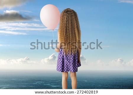 Little girl holding balloon - stock photo