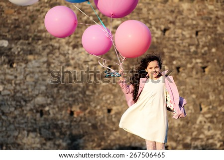 Little girl holding balloons looking forward, outdoor horizontal photo - stock photo