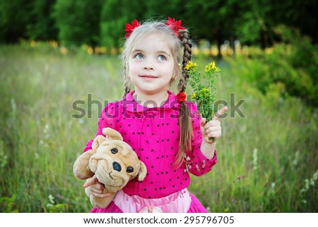 little girl holding dog outdoors - stock photo