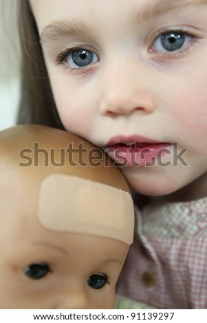 Little girl holding doll - stock photo