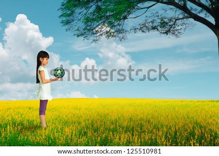 Little girl holding earth with recycle symbol at flower field, Elements of this image furnished by NASA - stock photo