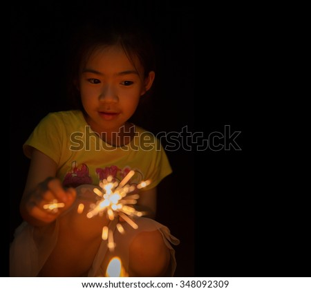 little girl holding fireworks on black background for new year holiday party - stock photo