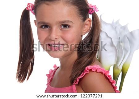 Little girl holding flowers behind back - stock photo