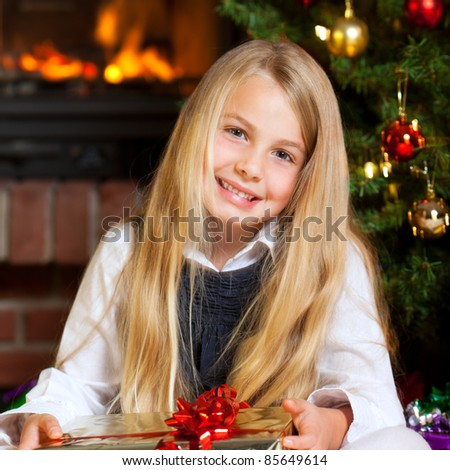 little girl holding gift christmas tree and fire place in background - stock photo