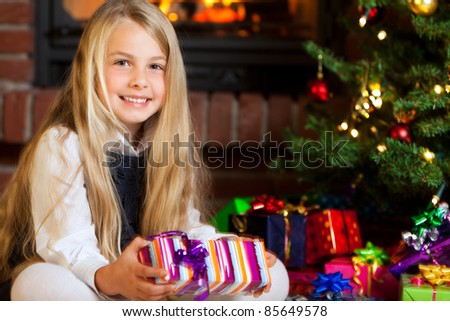 little girl holding gift christmas tree with many gifts and fire place in background - stock photo