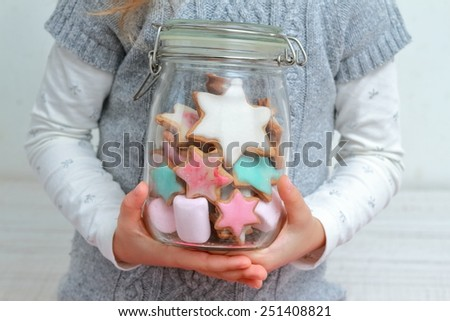 Little girl holding glass jar with sweets inside - stock photo