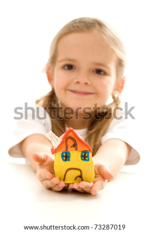 Little girl holding her clay house - happy home concept, isolated