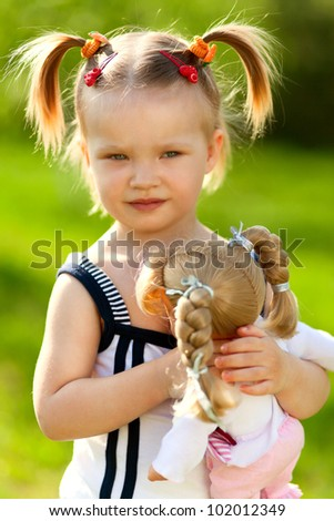 little girl holding her doll in the park - stock photo