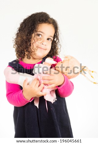 Little girl holding her doll, isolated on white background  - stock photo