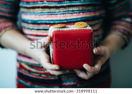 Little girl holding modern Christmas presents - stock photo