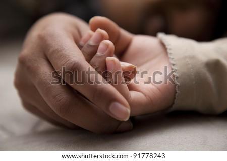 Little girl holding mom's hand as she sleeps - stock photo