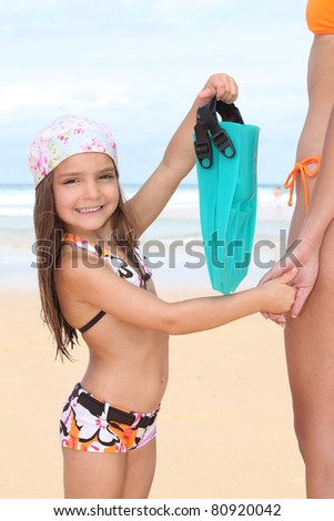 little girl holding mother's hand and showing flippers bag - stock photo