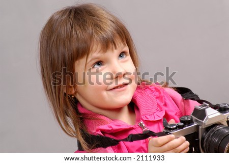 little girl holding old-style camera
