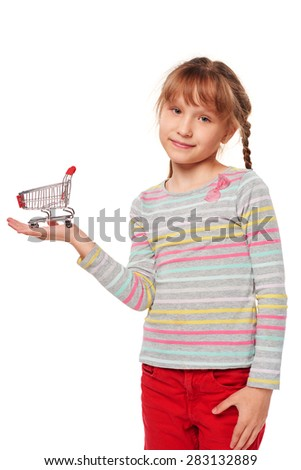 Little girl holding small empty shopping cart on her palm, over white background - stock photo