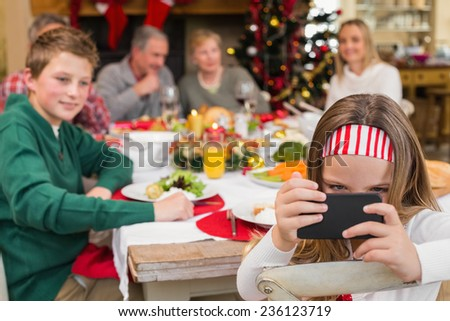 Little girl holding smartphone during christmas dinner at home in the living room - stock photo