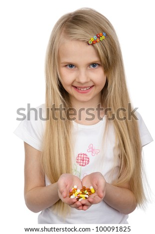little girl holding some pills. isolated on white background - stock photo