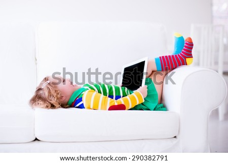Little girl holding tablet pc relaxing on a white couch. Kids using computer at home or preschool. Children learning with digital devices. Child playing online game. Toddler kid and modern gadget. - stock photo