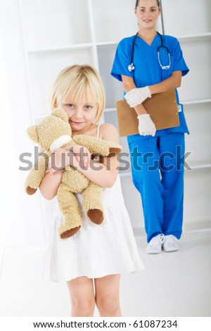 little girl holding teddy bear in doctor's office