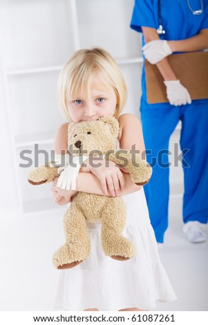 little girl holding teddy bear in doctor's office - stock photo