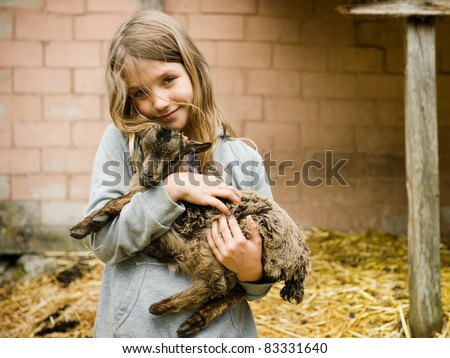 Little girl holding the small goat