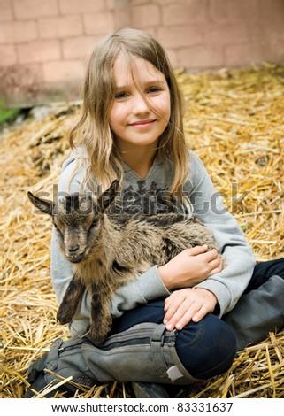 Little girl holding the small goatling - stock photo