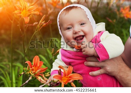 Little girl holding the weight looking at the camera, playing with Lily, laughing, having fun, warm summer day in nature