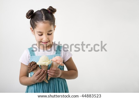 little girl holding three cones with chocolate, vanila and strawberry ice cream scoops - stock photo