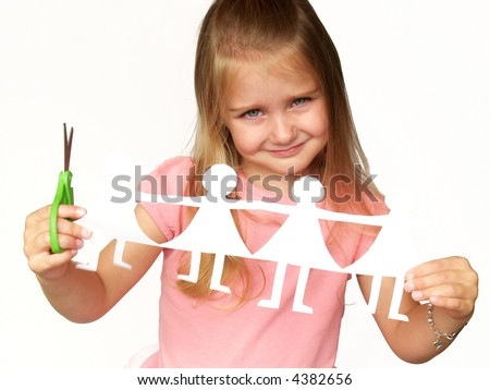 little girl holding up paper dolls and scissors - stock photo