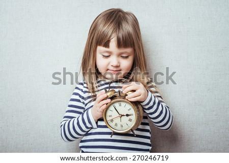 Little girl  holding vintage clock - stock photo