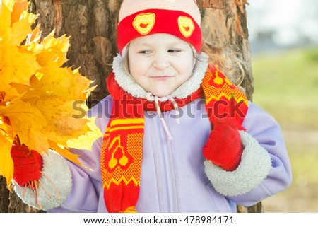 Little girl holding yellow with gold autumn leaves bunch in hand outdoor portrait