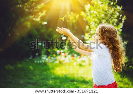 Little girl holding young green plant in sunlight. Ecology concept. Background toning to instagram filter. - stock photo