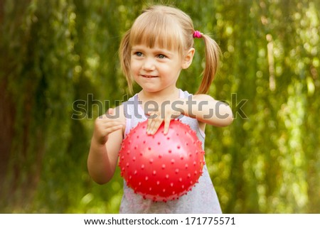 Little girl holds a pink ball - stock photo