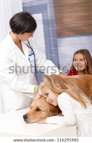 Little girl huddling up against pet dog's head at veterinarian during examination.
