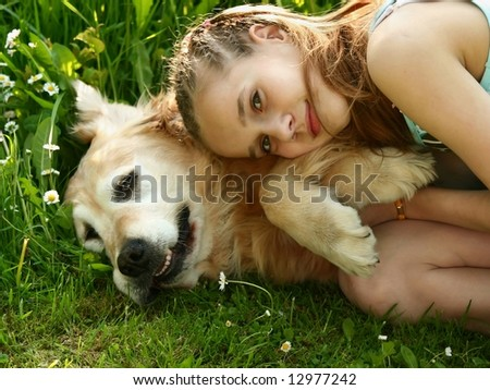 Little girl hugging a big dog in an outdoor setting - stock photo