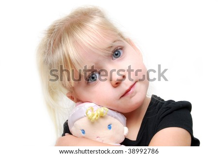 little girl hugging a doll - stock photo