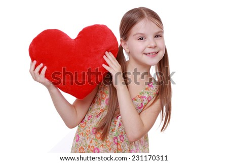 Little girl hugging a large red heart symbol isolated on white background