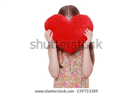 Little girl hugging a large red heart symbol isolated on white background - stock photo
