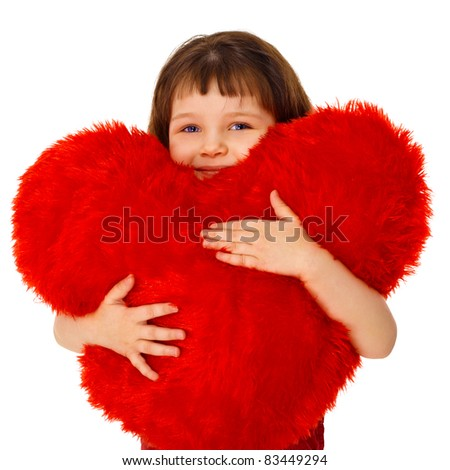 Little girl hugging a large toy heart isolated on white background - stock photo