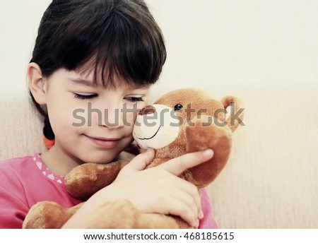 Little girl hugging a teddy bear in the room.