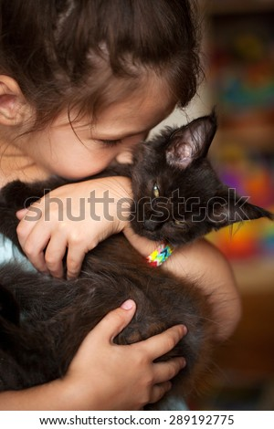 Little girl hugging and kissing a black kitten Maine Coon - stock photo