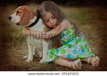 little girl hugging dog outdoors - stock photo