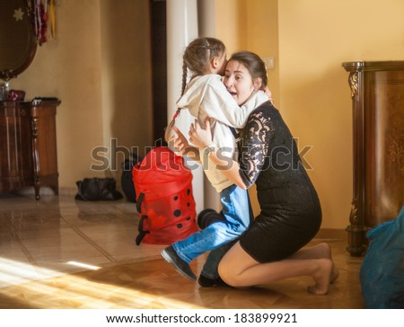 Little girl hugging her mother after school at home - stock photo