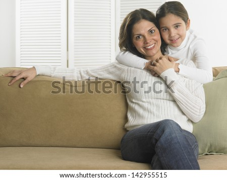 Little girl hugging her mother from behind