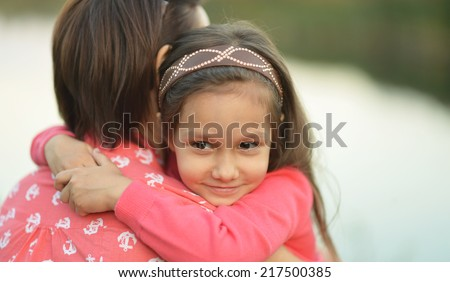 Little girl hugging her mother near the lake - stock photo