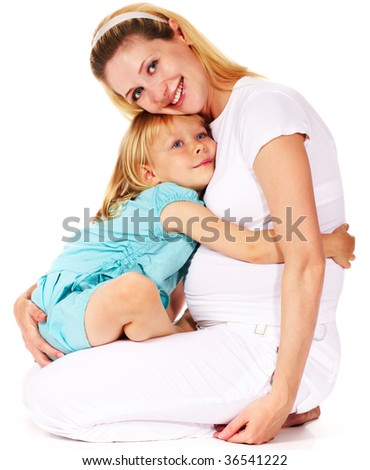 little girl hugging her pregnant mother - stock photo