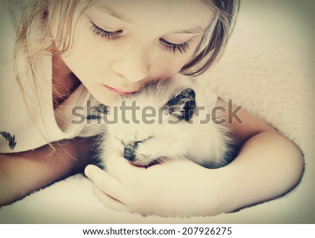 little girl hugging kitten  - stock photo