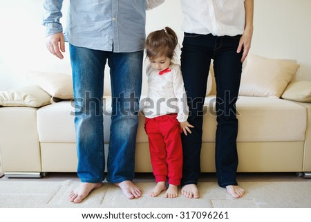little girl hugging mom and dad for legs