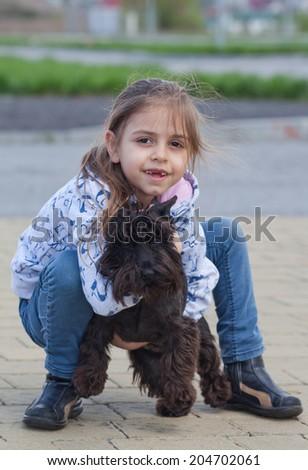 Little girl hugging 6 month old  miniature schnauzer puppy sitting on pavement - stock photo