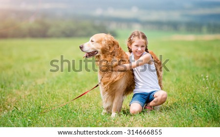 Little girl hugging  retriever in the summer park - stock photo